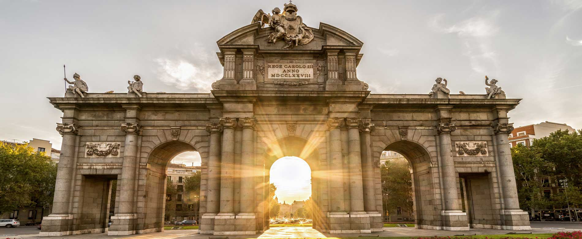 Puerta de Alcalá, surrounded by gardens and pierced by the evening sun.